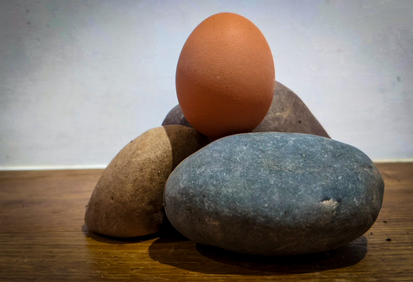 Image of an egg on top of three different coloured stones