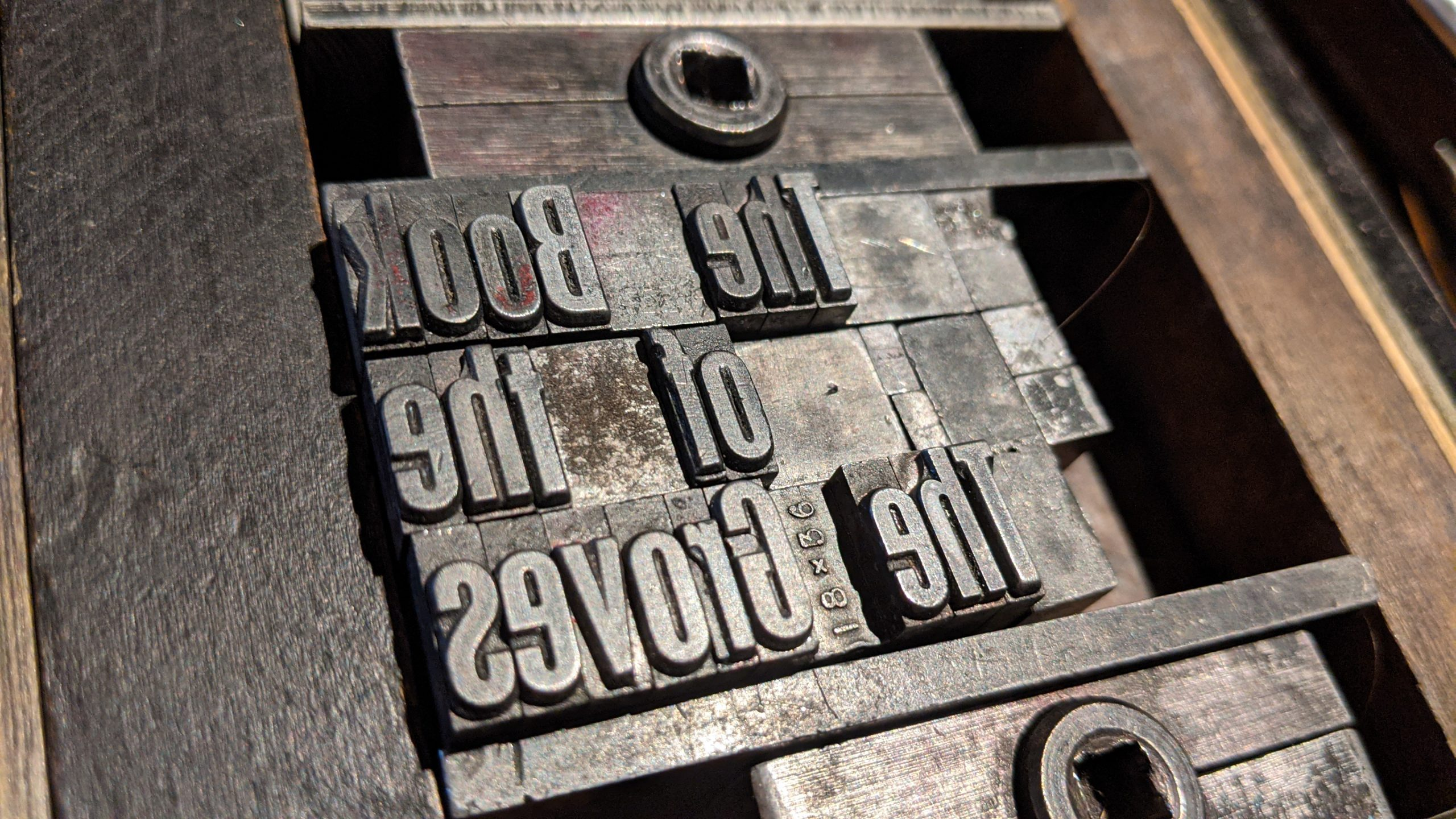 Image of a printing forme with letterpress type spelling out The Book Of the Groves